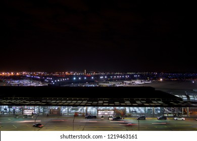 CHICAGO, ILLINOIS, UNITED STATES - MAY 11th, 2018: Outside of Chicago O'Hare International Airport at night with some cars and airplanes at the terminal
