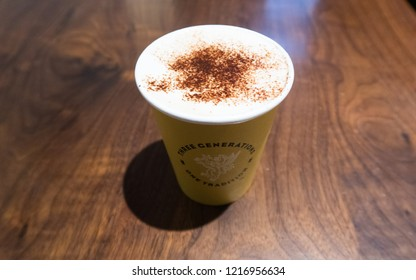 Chicago, Illinois, United States - October 8, 2018: Caffe Umbria cappuccino in a yellow takeout paper cup.