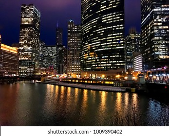 Chicago, Illinois / USA - 01/24/2018: City night lights reflect onto an almost frozen Chicago River during evening rush hour commute in winter.