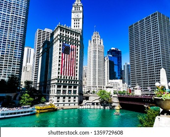 Chicago, Illinois, USA. 07 06 2018. Wrigley building with large american flag on 4th July week. River watefront.