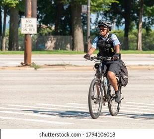 Chicago, Illinois / USA - July 4 2020: A female police officer patrolling Chicago Downtown biking along Michigan Lake - Chicago Police Bicycle Patrol.