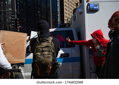 Chicago, Illinois / USA -5/30/2020: Protest for George Floyd, A group of angry protestors crowds a police vehicle and spray paints it.