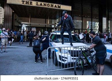 Chicago, Illinois / USA -5/30/2020: Protest for George Floyd, A person stands on a police car during protest.