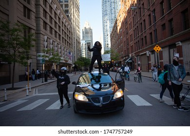 Chicago, Illinois / USA -5/30/2020: Protest for George Floyd, A woman stands on a car in protest.