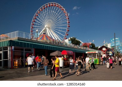 Chicago, Illinois, USA – August 02, 2009: Horizontal beautiful summer shot of the visitors of the colorful Navy Pier waterfront and its retro Ferris wheel before its last remodeling