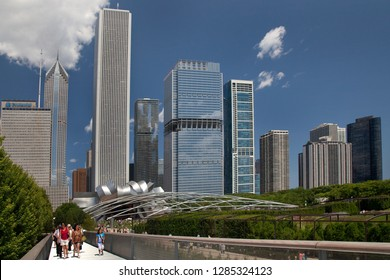 Chicago, Illinois, USA – August 02, 2009: People crossing Renzo Piano Nichols Bridgeway, with Chicago skyline and Frank Gehry auditorium (Pritzker Pavilion) as background, Millenium Park