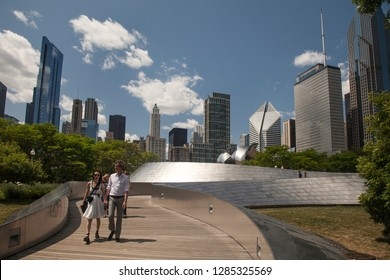 Chicago, Illinois, USA – August 02, 2009: Horizontal shot of a couple crossing the Frank Gehry BP Pedestrian Bridge, with the Chicago skyline as background, Millenium Park