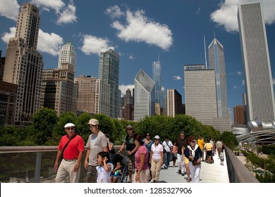 Chicago, Illinois, USA – August 02, 2009: Horizontal lateral close up view of some people crossing the Renzo Piano Nichols Bridgeway, with the Chicago skyline as background, Millenium Park