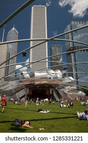Chicago, Illinois, USA – August 02, 2009: Vertical view of some people lying on the grass of the Frank Gehry auditorium (Pritzker Pavilion) lawn, with the Chicago skyline as background, Millenium Park