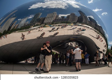Chicago, Illinois, USA – August 02, 2009: Horizontal shot of some tango dancers at Anish Kapoor Cloud Gate (The Bean) sculpture, with aChicago skyline reflection background, Millenium Park