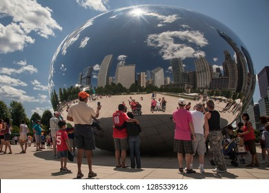 Chicago, Illinois, USA – August 02, 2009: Horizontal shot of people self portraying their reflections, with Chicago skyline background, at Anish Kapoor Cloud Gate (The Bean) sculpture, Millenium Park