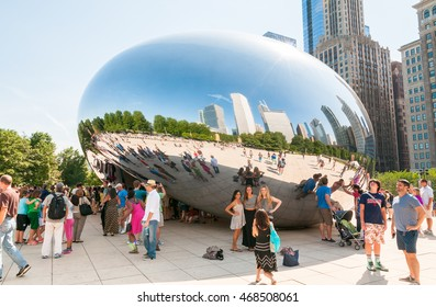 Chicago, Illinois, USA - August 15, 2014: Tourists visiting Cloud Gate, one of the most unique and interesting sculptures in decades graces the promenade at Chicago Millennium Park.