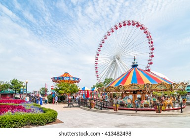 Chicago, Illinois, USA - August 24, 2014: Tourists at the amusement park on Navy Pier. Navy Pier's Ferris wheel.