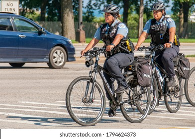 Chicago, Illinois / USA - August 4 2020: Two female police officers patrolling Chicago Downtown biking along Michigan Lake - Chicago Police Bicycle Patrol.