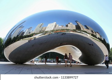 """CHICAGO, ILLINOIS, USA - AUGUST: Tourist and visitors interact with """"The Bean"""" aka """"Cloud Gate"""" a popular tourist attraction at Millennium Park in downtown Chicago, as seen on August 17, 2015."""