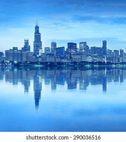 Chicago Illinois USA, blue color processed panorama of city downtown skyline at sunset with illuminated buildings, park and lake reflections