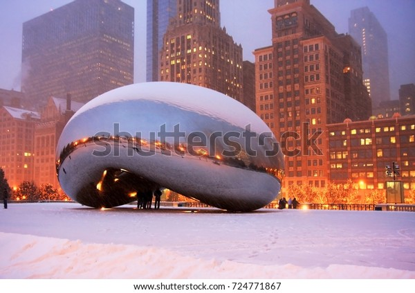 CHICAGO, ILLINOIS, USA - DECEMBER 16,2008: Beautiful snowy winter night in the center of Chicago.People enjoying Millennium park during December 16,2008 evening.Street lights reflect in a Cloud Gates.