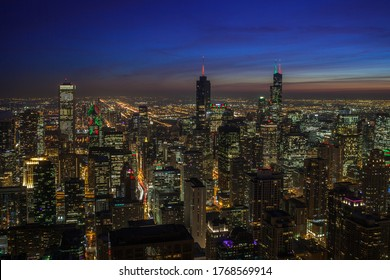 Chicago, Illinois, USA - December 23, 2019:  Aerial view of Chicago at twilight from the John Hancock building.  Skyscrapers illuminated with Christmas colored lights are seen