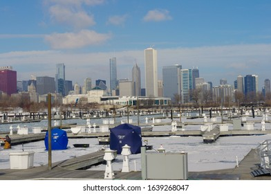 Chicago, Illinois / USA - February 22 2015 : Fisherman on frozen Michigan Lake, with Chicago skyline as a background.  Fishing on ice in a sunny Icy and cold Winter day.