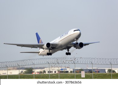 Chicago, Illinois / USA - July 12, 2015 - View of a United Airlines Boeing 767 taking off from runway 22L at Chicago O'Hare International Airport.  Aircraft is about to pass airport boundary fence.