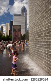 Chicago, Illinois, USA – July 27, 2014: Vertical shot of a child refreshing at Jaume Plensa Crown fountain with the Chicago skyline as background, Millenium Park