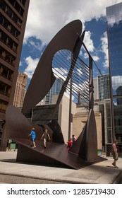 Chicago, Illinois, USA – July 27, 2014: Vertical shot of two children walking over the Picasso Untitled sculpture at Daley Plaza in the Loop