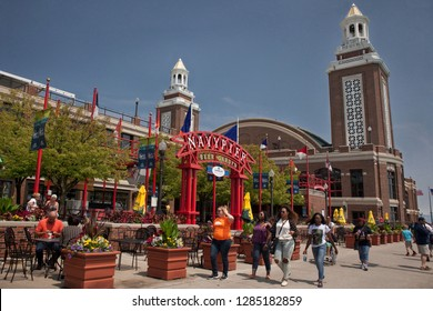 Chicago, Illinois, USA – July 28, 2014: Horizontal shot of four girls passing by the Miller Lite Beer Garden with the Aon Grand Ballroom in the background, Navy Pier on a sunny day