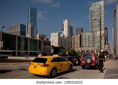 Chicago, Illinois, USA – July 28, 2014: Horizontal colorful view of Randolph St with some cars in the foreground and Heritage at Millenium Park and Pittsfield Building in the background, Chicago Loop