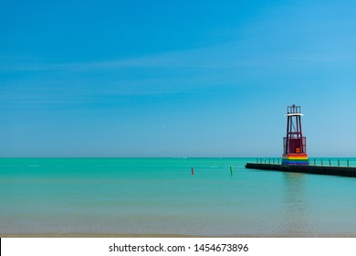 Chicago, Illinois / USA - July 9 2019: Lake Michigan and a Light Beacon painted with the Rainbow Gay Pride Flag at Kathy Osterman Beach in Edgewater Chicago