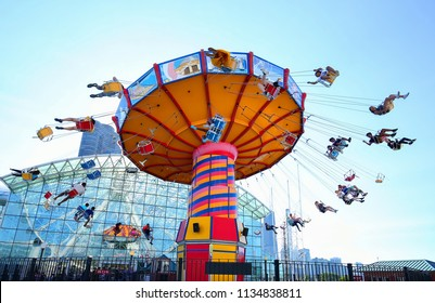 CHICAGO, ILLINOIS, USA - JULY:   Adults and kids scream as the Navy Pier Wave Swinger Ride spins them into the air as seen on July 2, 2018.