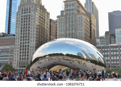 Chicago, Illinois, USA - June 11, 2018: Cloud Gate - Bean in Millenium Park in downtown with reflection in summer. Modern cityscape with tourists on background. Famous architecture landmark.
