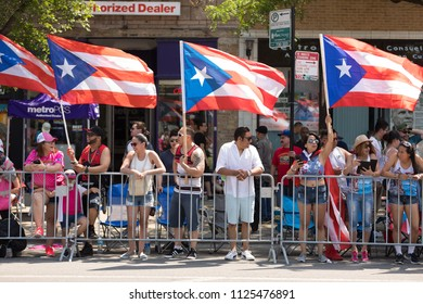 Chicago, Illinois, USA - June 16, 2018 A group of spectators wave the Puerto Rican flag during the Puerto Rican People's Parade