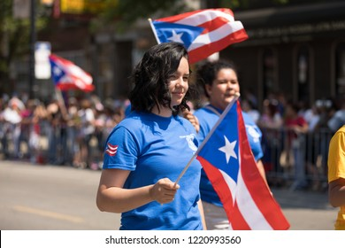 Chicago, Illinois, USA - June 16, 2018: The Puerto Rican People's Parade, Puerto rican woman waving the puerto rican flag going down the road during the parade