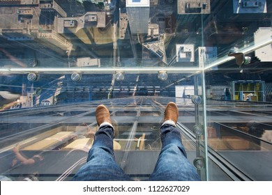 Chicago, Illinois, USA - June 2016: Looking down from the glass box ledge of the Willis Tower skydeck, with downtown Chicago visible beneath the glass floor
