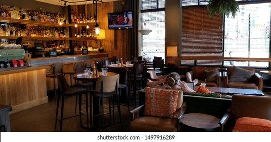 Chicago, Illinois / USA - June 23 2019: An interior shot of a woman on her phone at Beatrix Fulton restaurant.