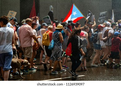 CHICAGO, ILLINOIS USA - JUNE 30, 2018: Demonstrators at the Families Belong Together protest rally cool off via the fire department fanning them with water.