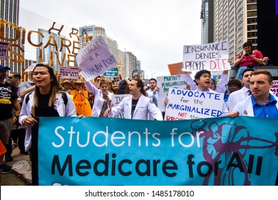 CHICAGO, ILLINOIS, USA - JUNE 8, 2019: Large group of people gather for the first ever Medicare For All Rally led by Bernie Sanders in downtown Chicago. Holding various signs and marching.