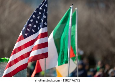 Chicago, Illinois, USA - March 16, 2019: St. Patrick's Day Parade, The American and the Irish flags transported down columbus drive at the parade