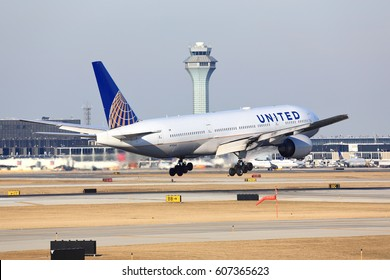Chicago, Illinois, USA - March 19, 2017: United Airlines Boeing 777-200 passenger jet airliner arriving for a landing at O'Hare International Airport in Chicago.  Control tower in the background