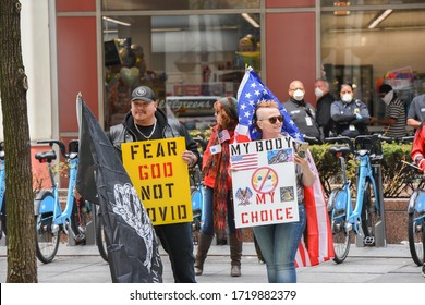Chicago, Illinois / USA - May 1,2020: Protesters gather in Chicago to protest the stay at home order issued by Governor J.B. Pritzker in front of the James R. Thompson Center demanding their rights.