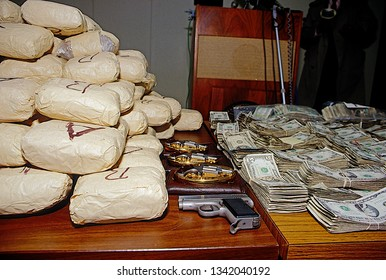 Chicago, Illinois. USA, May 18, 1987 Federal DEA agents display plies of cash and drugs, including kilos of  heroin and powder cocaine, along with weapons seized in recent raids across Chicago.