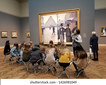 Chicago, Illinois / USA - May 22 2019: Shown here is a group of students learning about Paris Street; Rainy Day a large 1877 oil painting by the French artist Gustave Caillebotte.