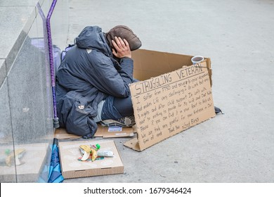 Chicago, Illinois, USA - october, 2019; Chicago city. Homeless veteran sitting on the roadside holding a cardboard sign, asking for help, downtown of Chicago, Illinous, USA.