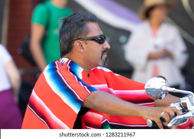 Chicago, Illinois, USA - September 15, 2018: Pilsen Mexican Independence Day Parade, Mexican man wearing a zarape, riding a motorcycle
