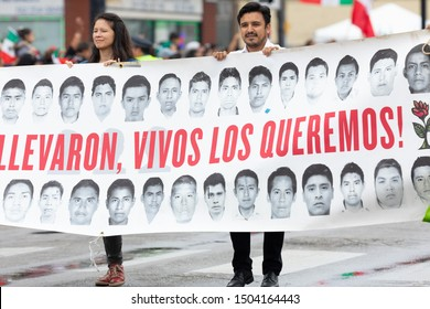 Chicago, Illinois, USA - September 8, 2019: 26th Street Mexican Independence Parade, Man and woman holding a banner with pictures of missing students Mexico,  Alive they Took them, Alive we want them