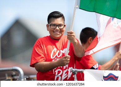 Chicago, Illinois , USA - September 9, 2018 The 26th Street Mexican Independence Parade, mexican boy waving a large mexican flag during the parade