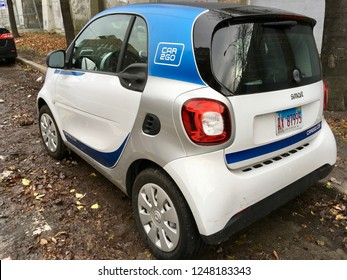 CHICAGO, ILLINOIS/DECEMBER 3, 2018: Car2Go vehicle parks on leaf covered pavement at near west side Green street hourly parking zone and railroad berm