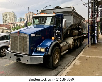CHICAGO, ILLINOIS/JUNE 4, 2019: Blue Kenworth diesel truck unloads soil mixture hopper into conveyor for transfer to courtyard renovation at near north side