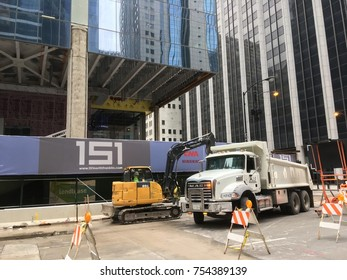 CHICAGO, ILLINOIS-NOVEMBER 11, 2017: Loader removes construction material into dump truck by new CNA office high rise project in Loop.