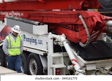 CHICAGO, ILLINOIS/USA â??OCTOBER 20, 2015: Concrete pumping crew worker sets up on Wacker Drive on October 20, 2015 in Chicago Loop